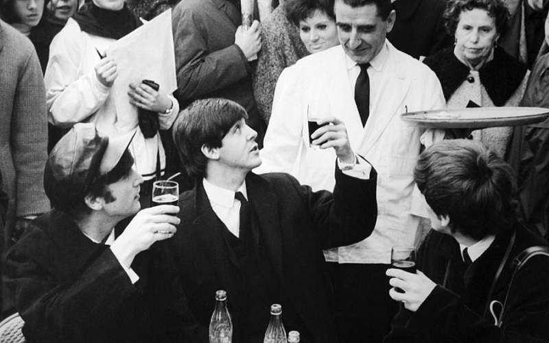 The Beatles have a drink in Paris, 1964.