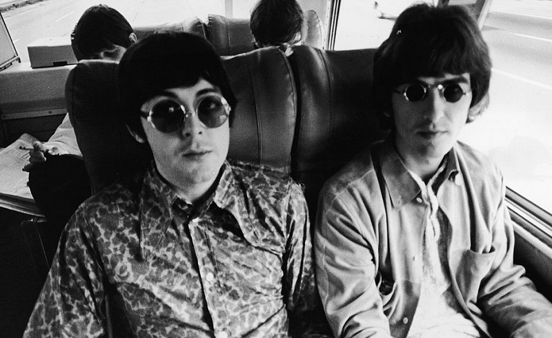 The Beatles' Paul McCartney and George Harrison ride in a bus in 1966.