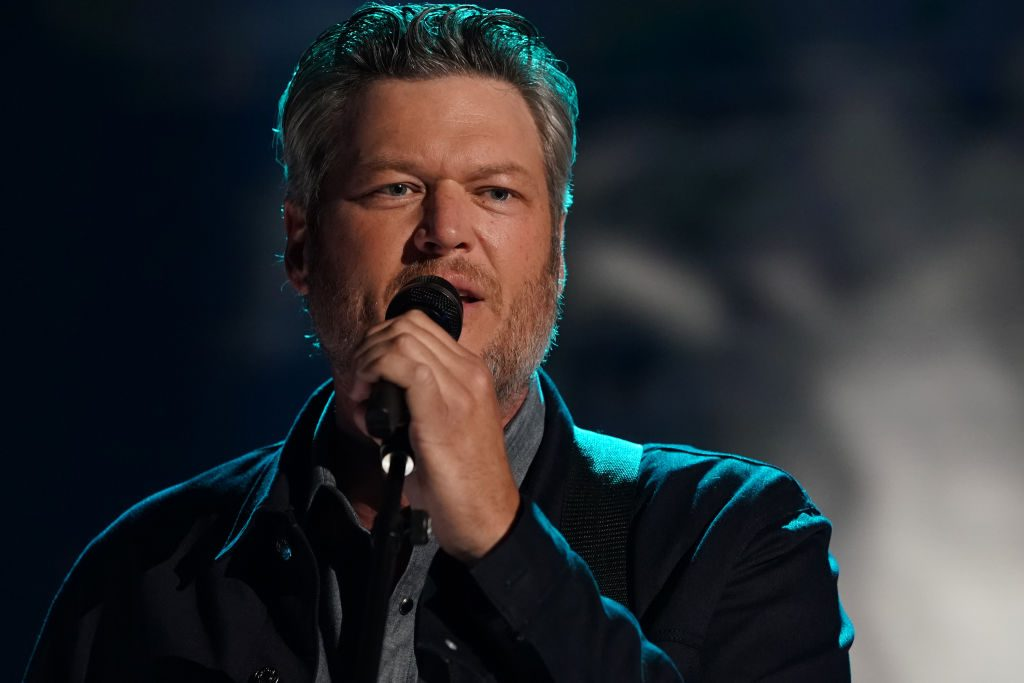 Blake Shelton is singing into a microphone