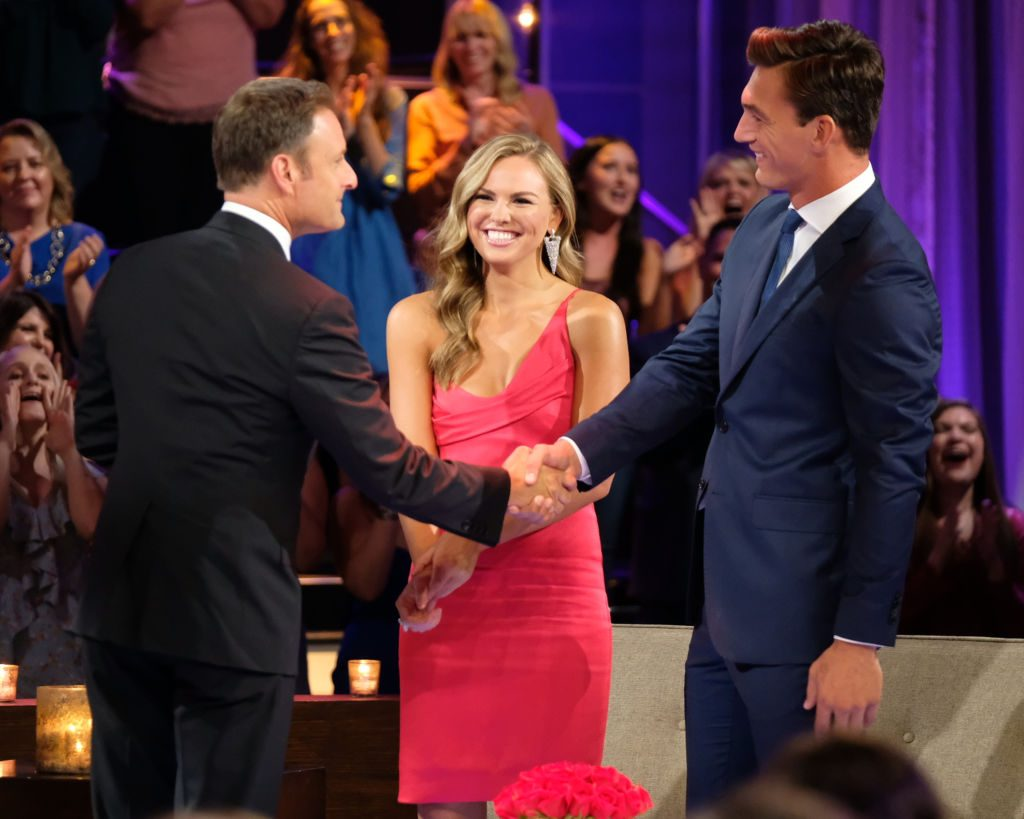 Chris Harrison and Tyler C. are shaking hands as Hannah Brown smiles on 'The Bachelorette'