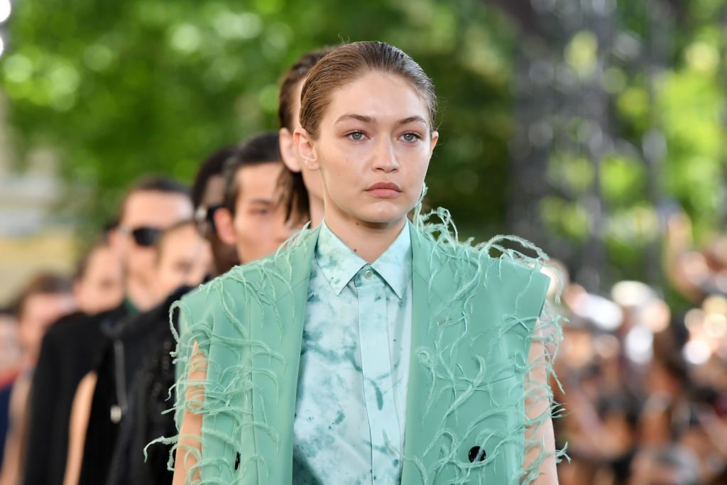 Gigi Hadid is in a suit on a runway.