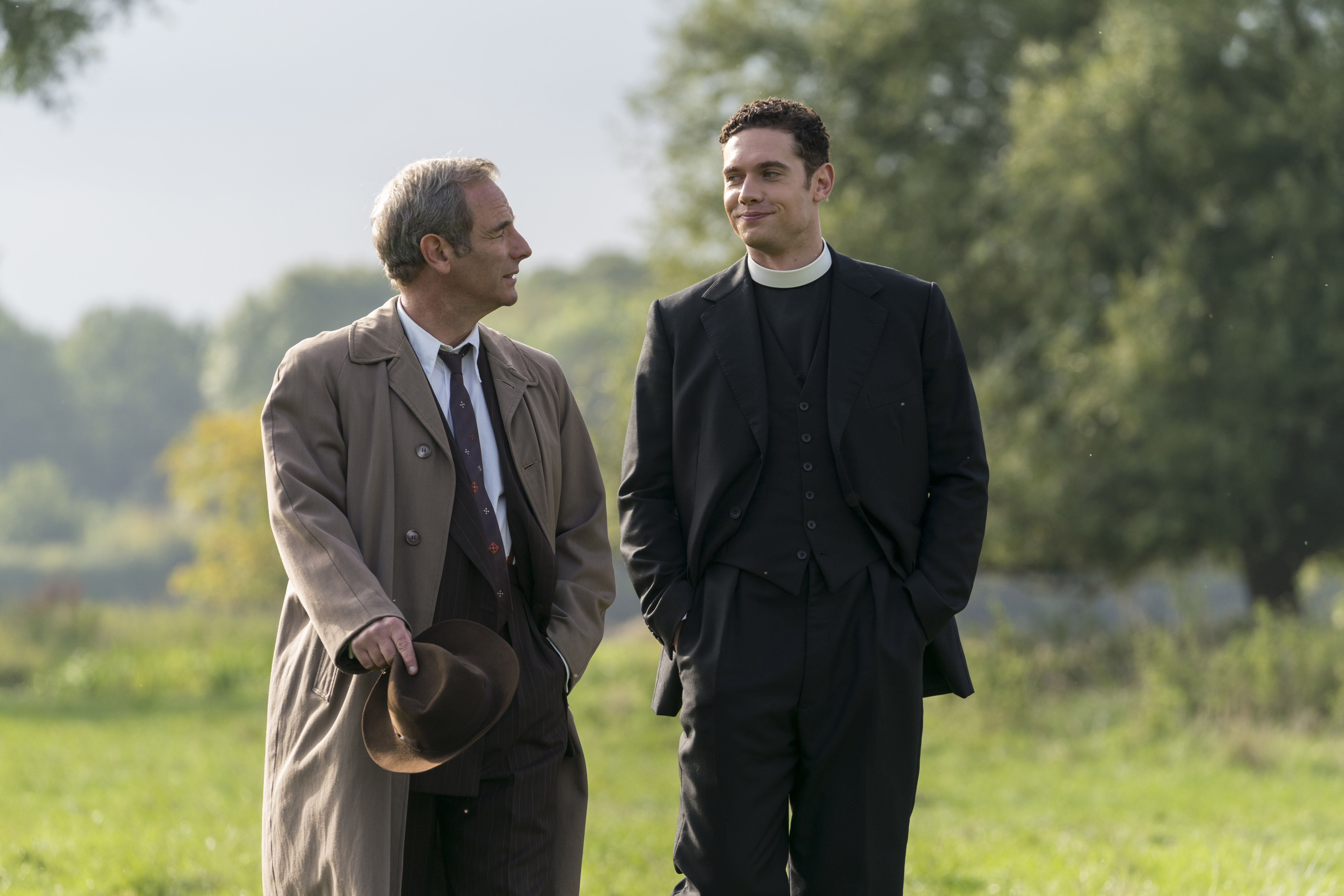 Robson Green and Tom Brittney smiling at each other in episode of 'Grantchester'