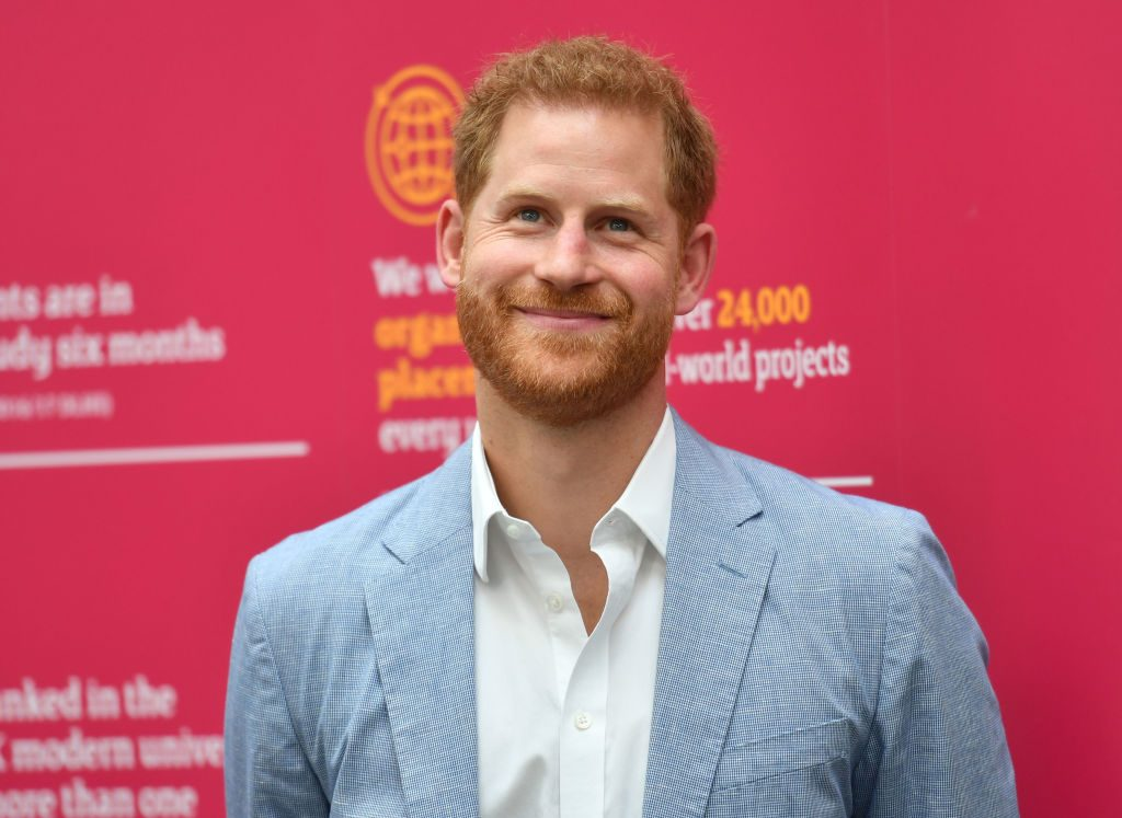 Prince Harry looks up and smiles.