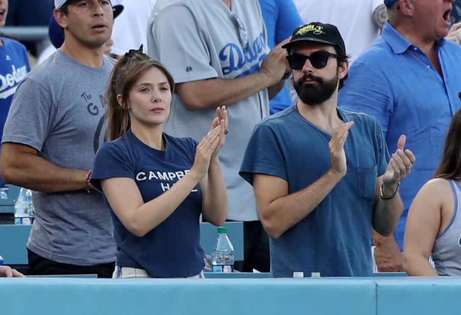 Elizabeth Olsen at a Dodgers game with boyfriend Robbie Arnett. An emerald ring is just visible on her left ring finger.