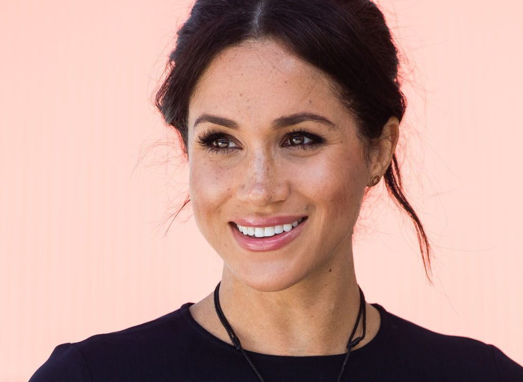 Close up shot of Meghan Markle smiling and looking off camera
