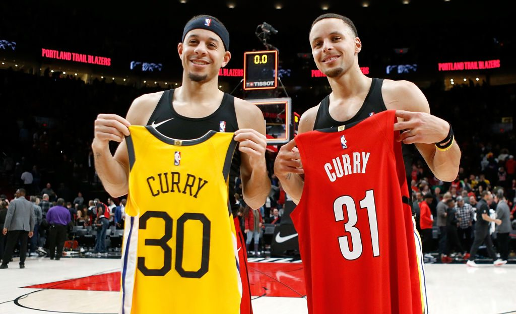 Brothers Seth and Steph Curry holding each other's basketball jerseys