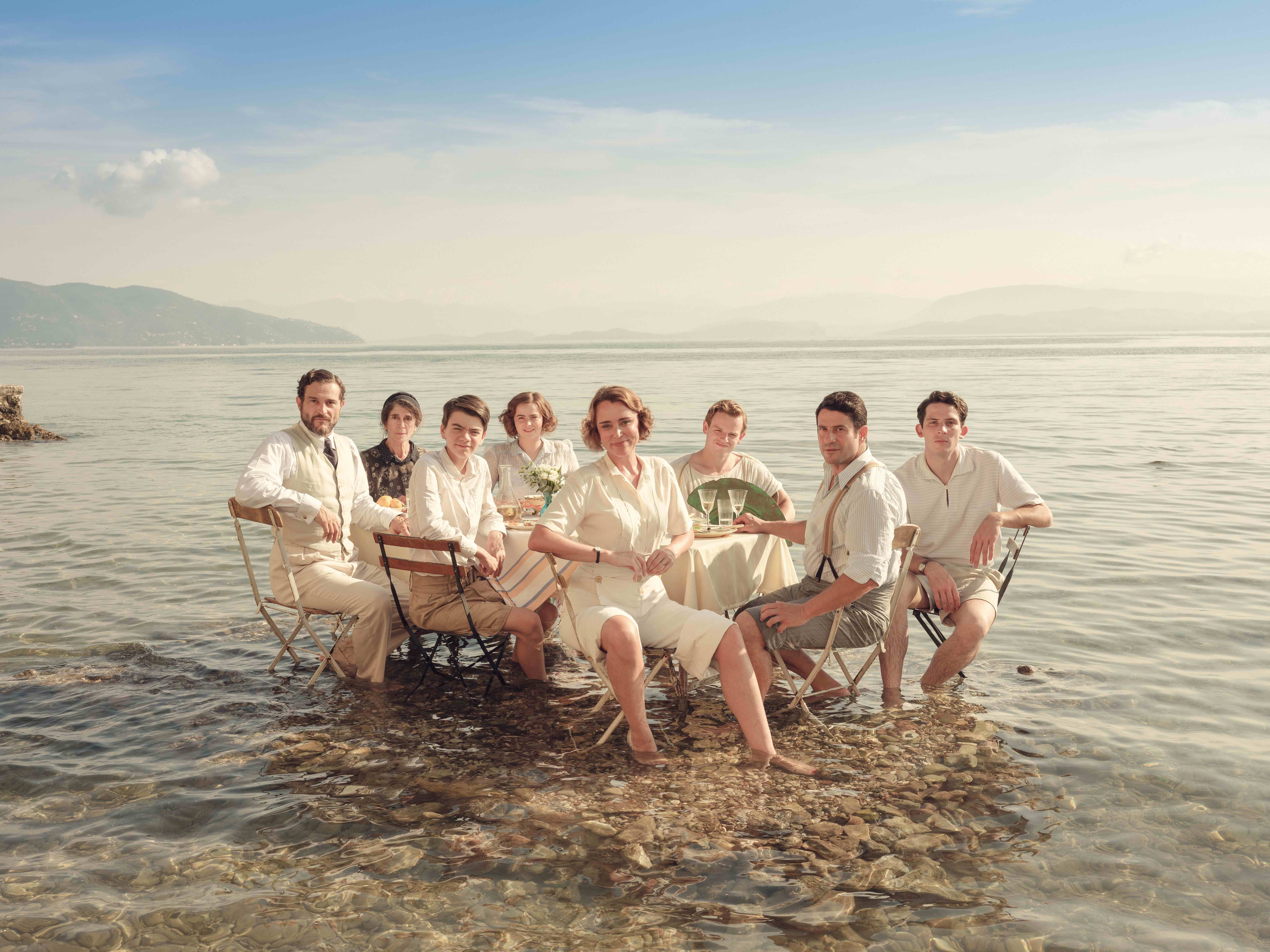 The Durrells sitting around a dining table in water