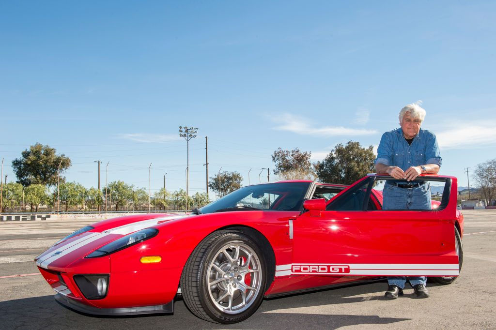 Jay Leno poses with a red Ford from his car collection