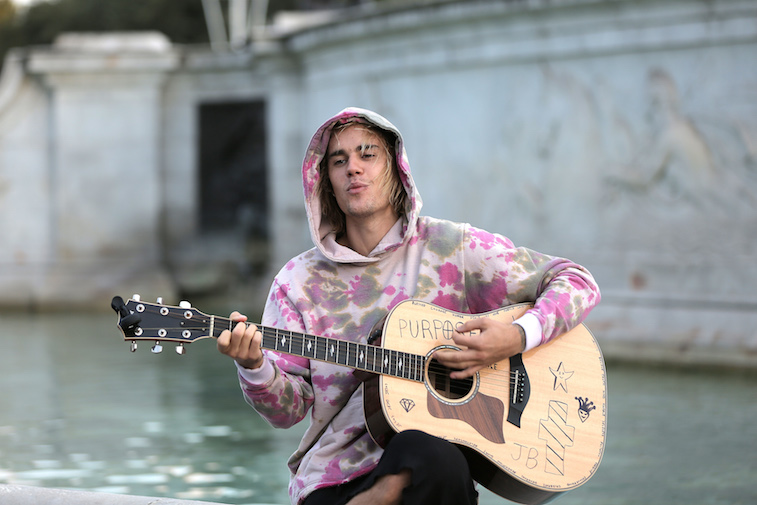 Justin Bieber playing guitar at the Buckingham Palace fountain.
