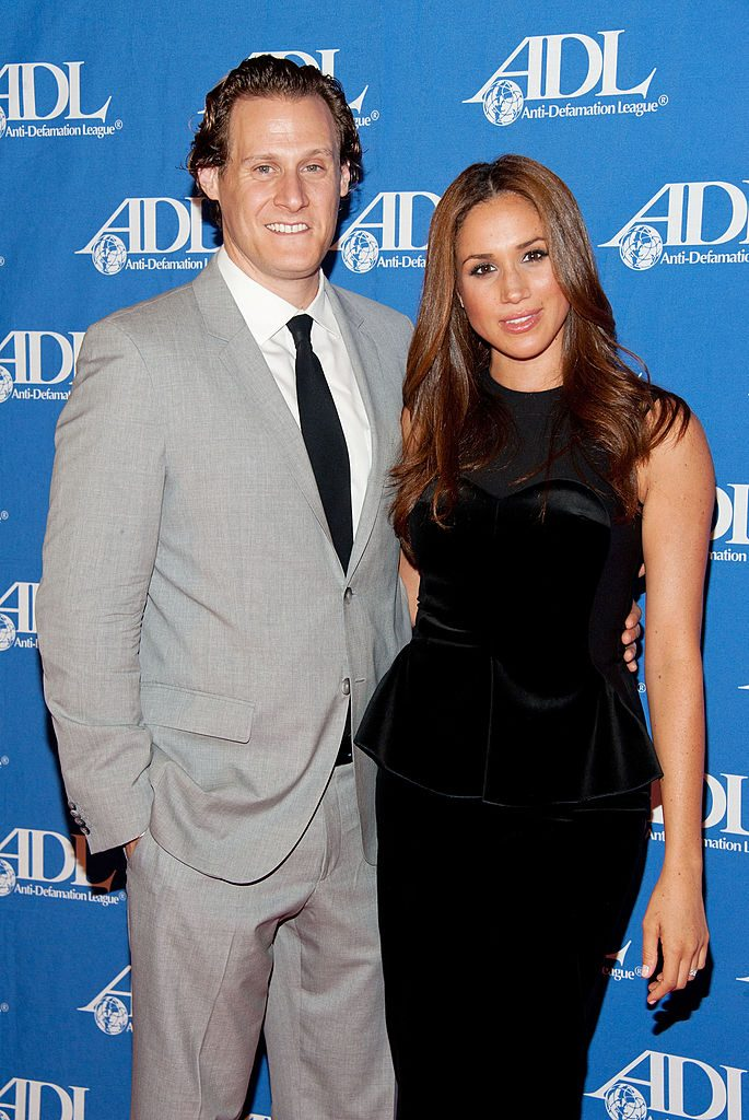 Trevor Engelson and Meghan Markle posing at an event