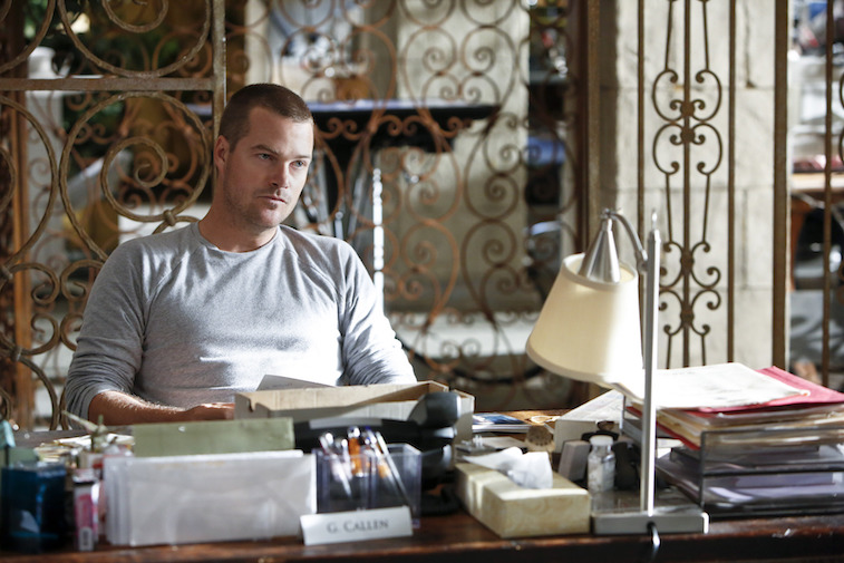 Chris O'Donnell sitting at a desk in Chris O'Donnell in NCIS: Los Angeles