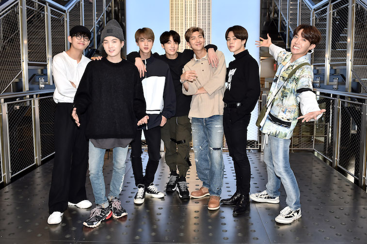 Members of the band BTS pose in front of the Empire State Building