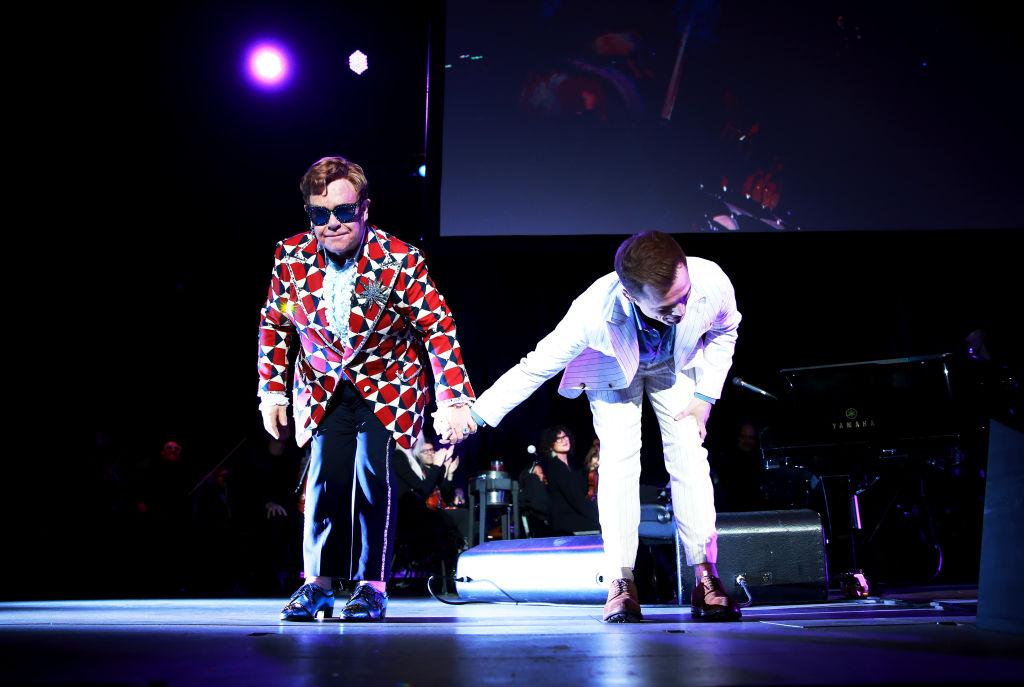 Elton John and Taron Egerton taking a bow after their performance