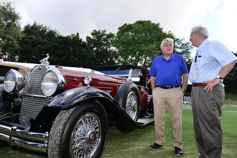 Jay Leno standing next to a car