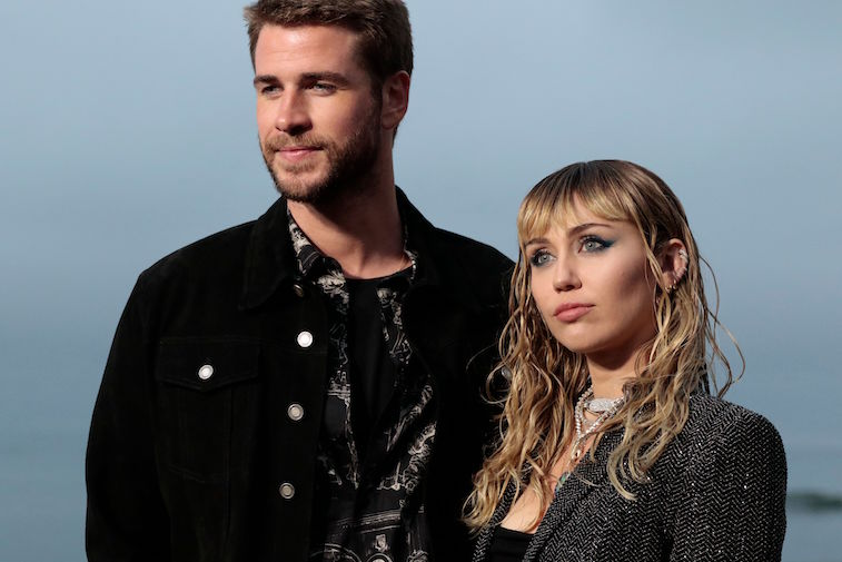 Liam Hemsworth and Miley Cyrus standing together