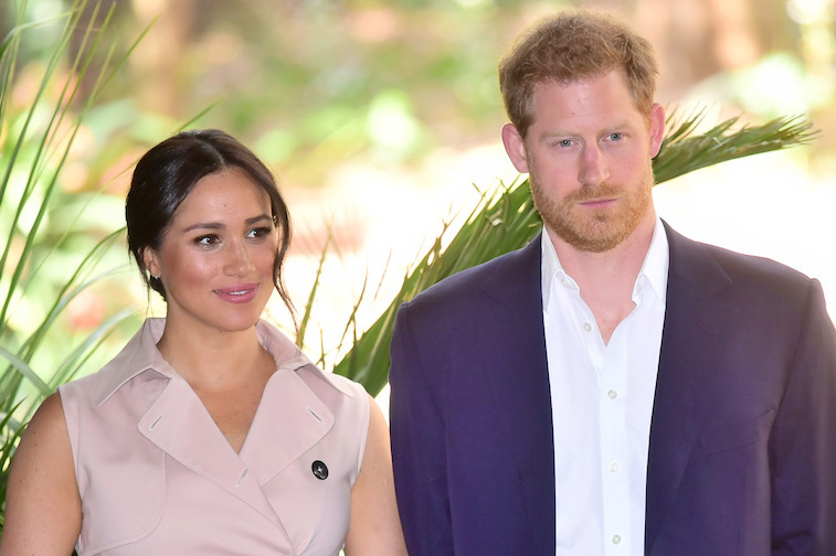 Prince Harry and Meghan Markle stand together smiling