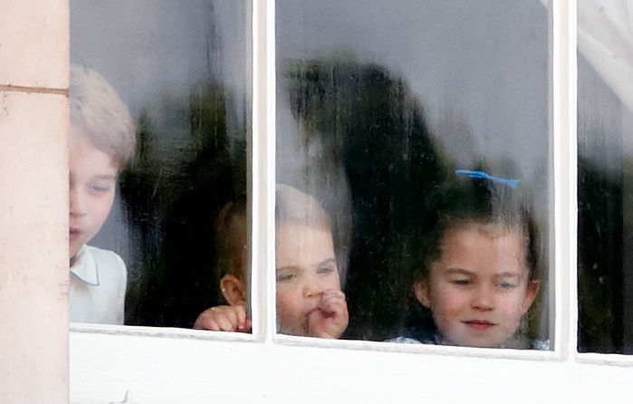 Prince George, Prince Louis, and Princess Charlotte looking through a window