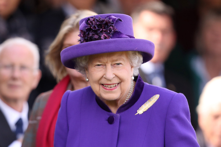 Queen Elizabeth II in a purple outfit and hat