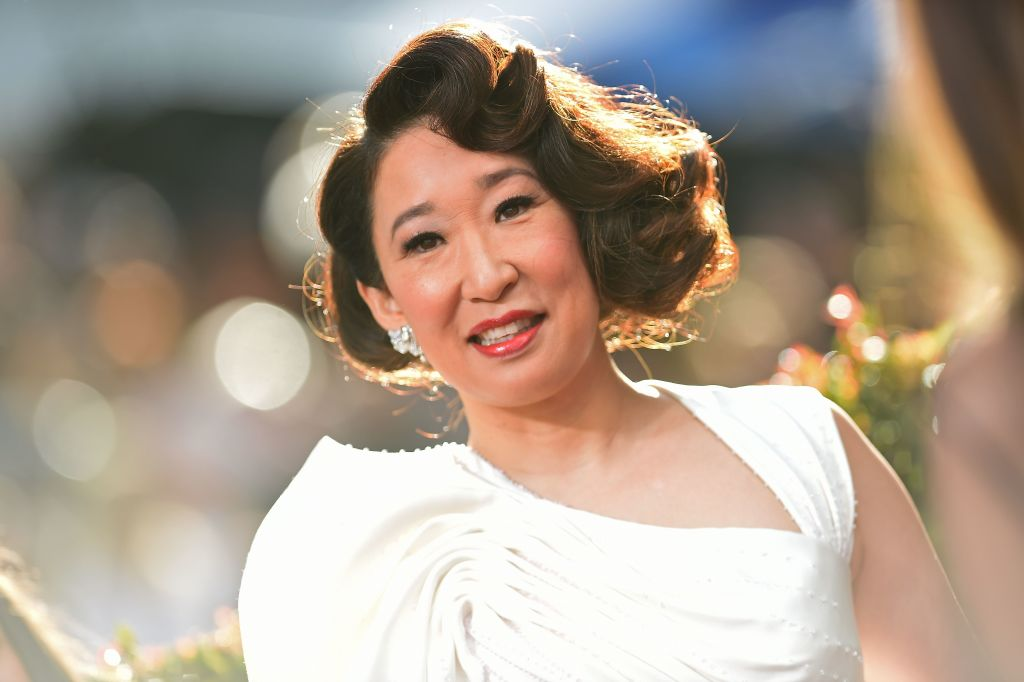 Sandra Oh smiles wearing a white gown at the Golden Globes