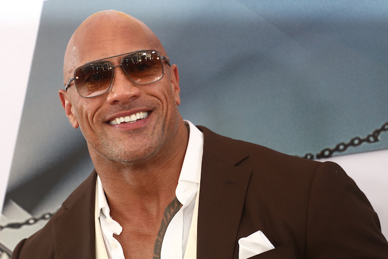 The rock wearing sunglasses smiling at the camera