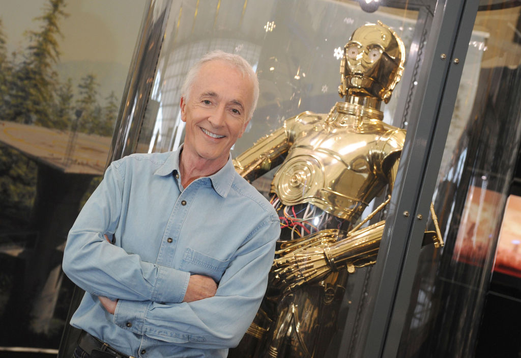 Anthony Daniels, the man behind C-3PO, standing next to the golden droid.