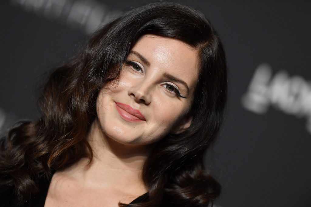 Lana Del Rey smiling and standing in front of a black background