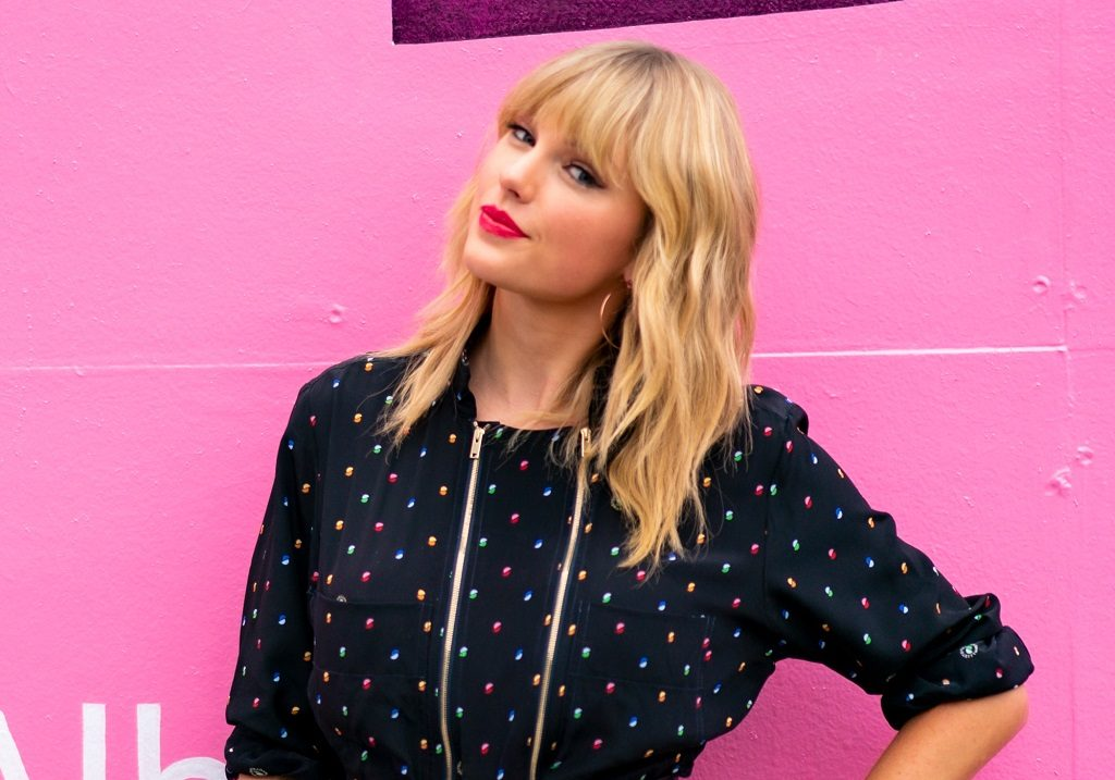 Taylor Swift poses in front of a mural for 'Lover' on August 23, 2019