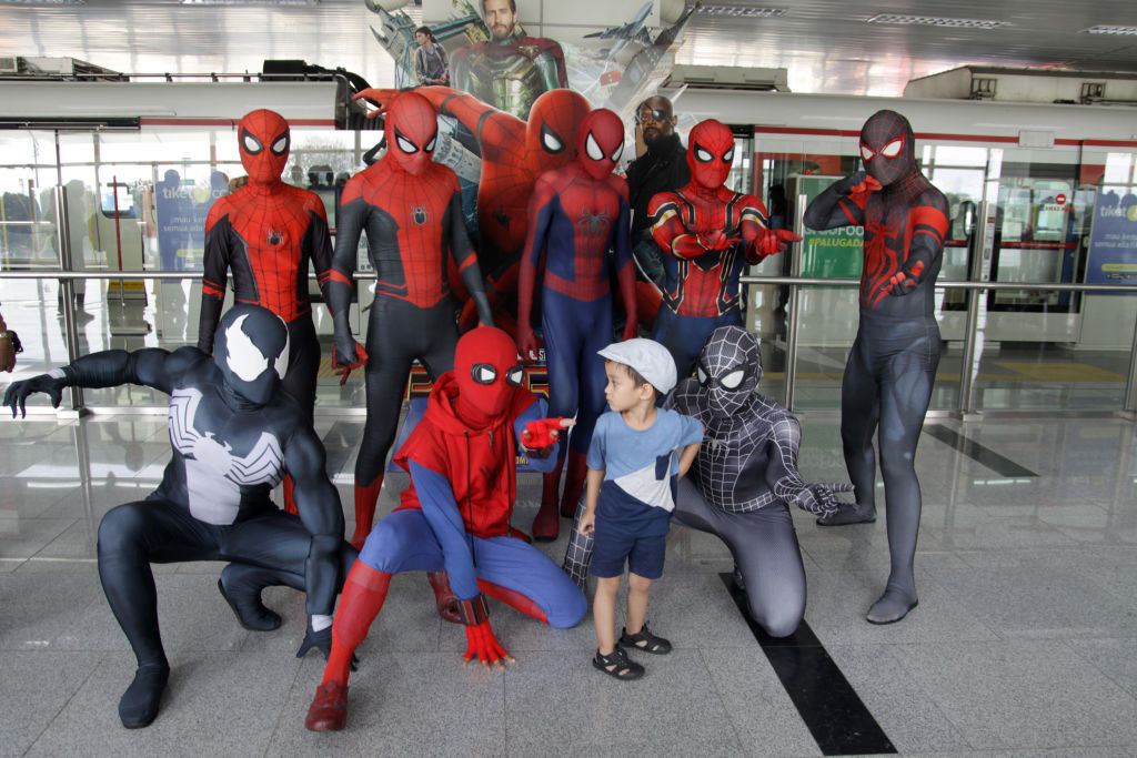 A group of cosplayers dressed as various versions of Spider-Man.