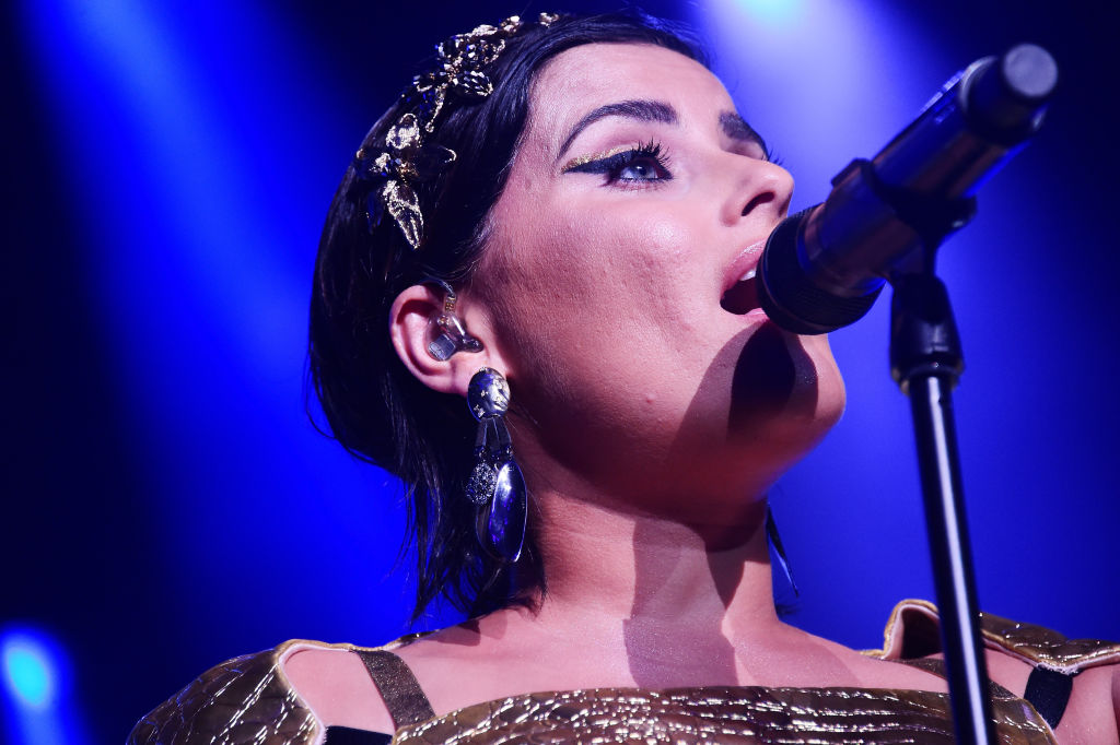 Nelly Furtado singing into a microphone.