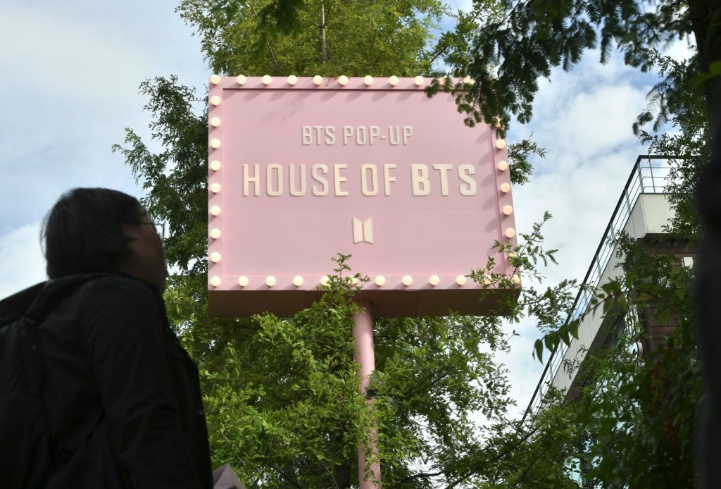A fan of South Korean K-pop boy band BTS stands outside a BTS pop-up store in Seoul