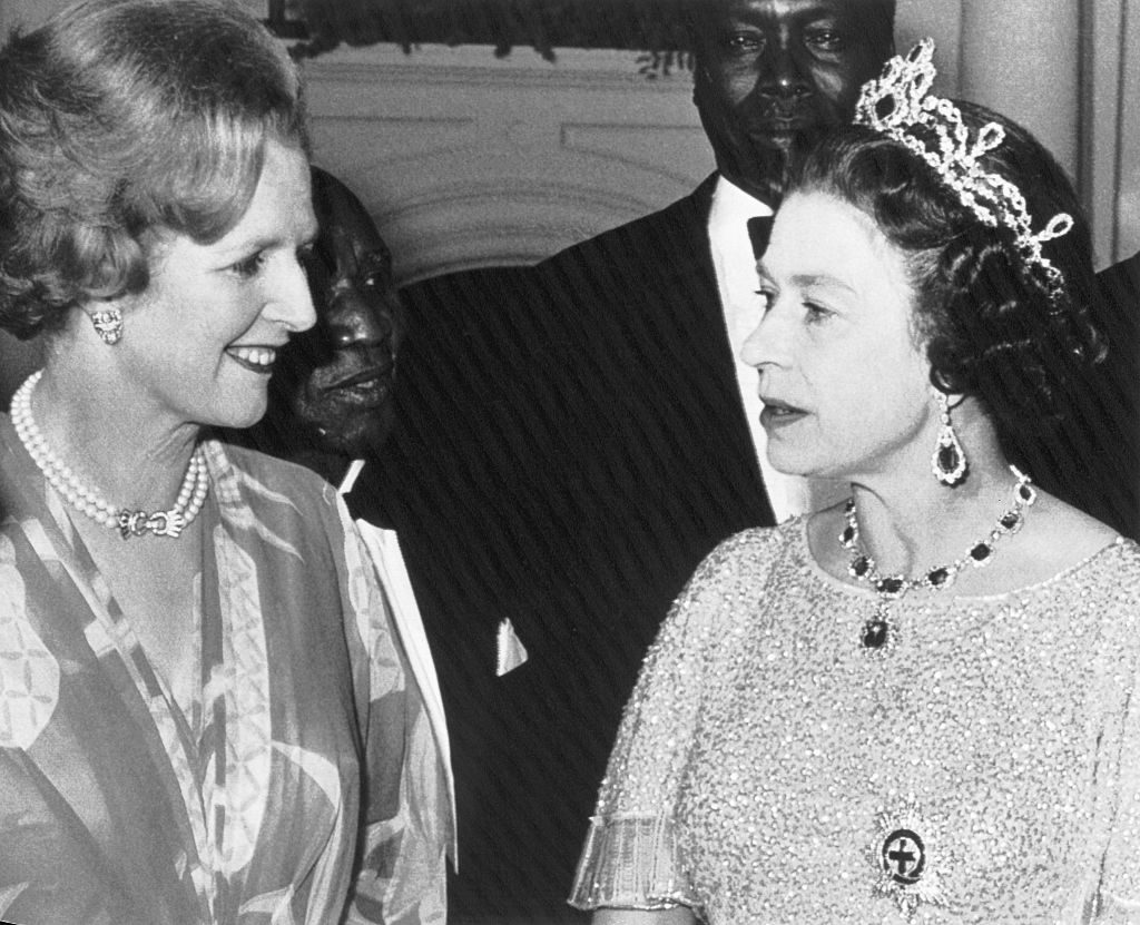 British Prime Minister, Margaret Thatcher(left), and Queen Elizabeth, chat at a party for the Heads of State gathered here for the Commonwealth Conference. Looking on in the rear are; Dr. Hasting Banda(left) of Malawi and Arap Moi of Kenya