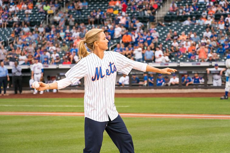 Tea Leoni throws a pitch at a baseball game