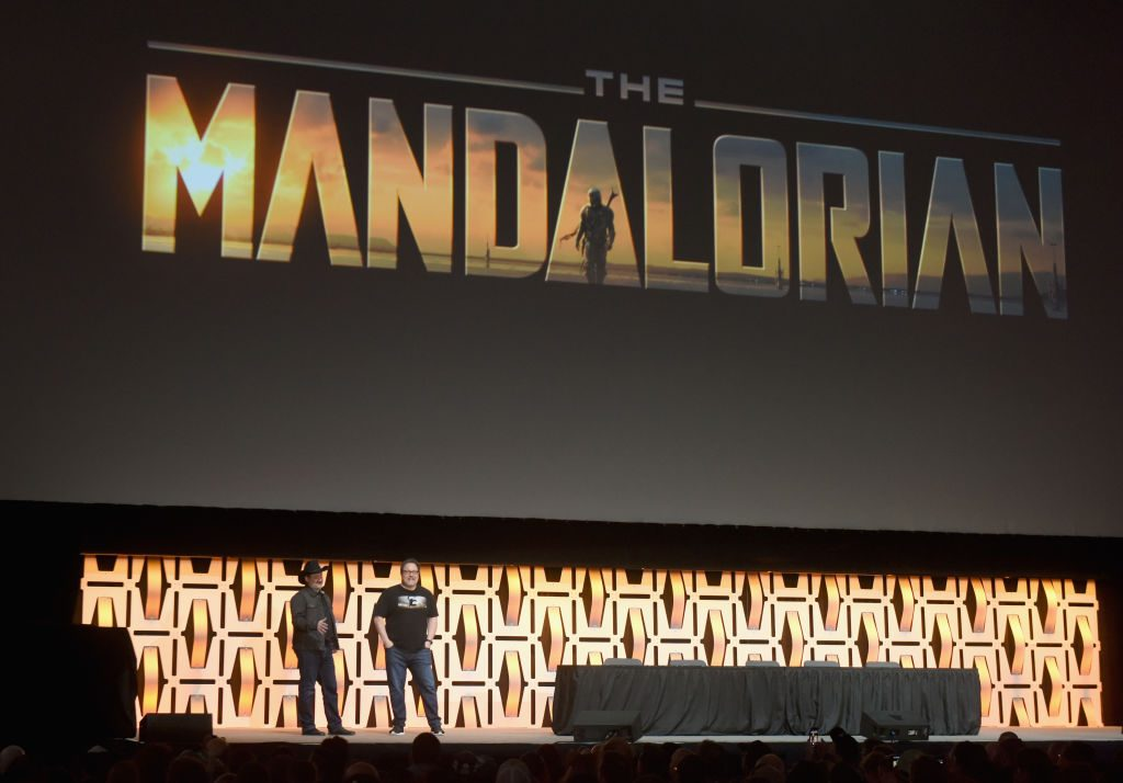 """Director/executive producer Dave Filoni (L) and Writer/executive producer Jon Favreau onstage during """"The Mandalorian"""" panel at the Star Wars Celebration"""