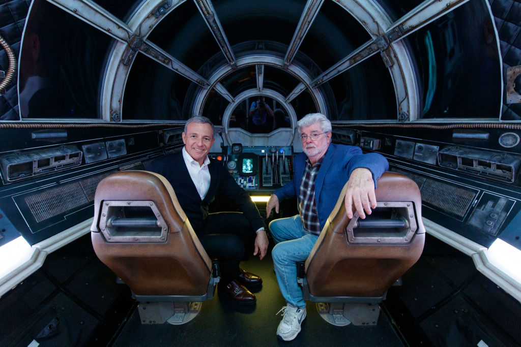 Bob Iger and George Lucas pose inside the Millennium Falcon ride at Disneyland's Galaxy Edge.