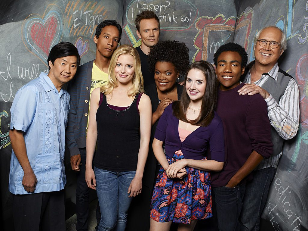 The Community cast huddle in a group for a promotional photo.