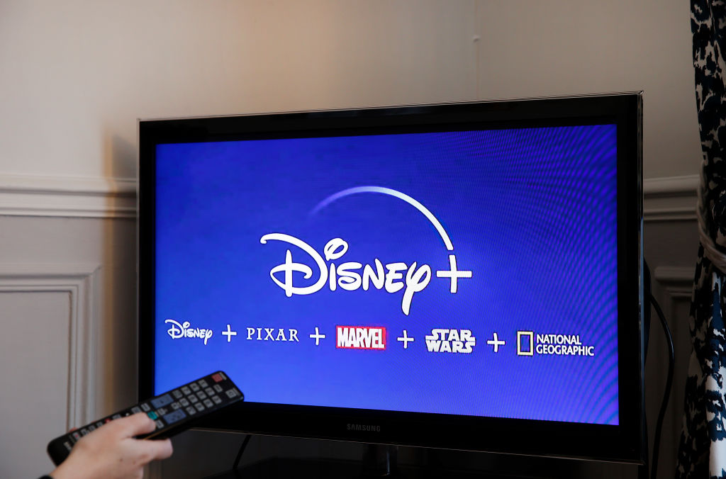 Someone turning on a TV with the Disney+ logo on it.