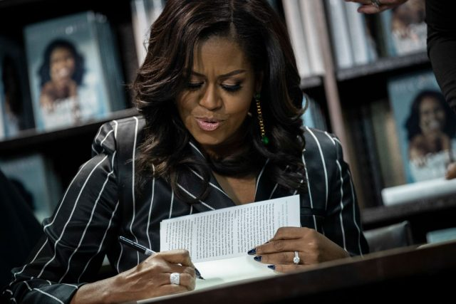 Michelle Obama signs copies of 'Becoming' during a book signing on Nov. 30, 2018