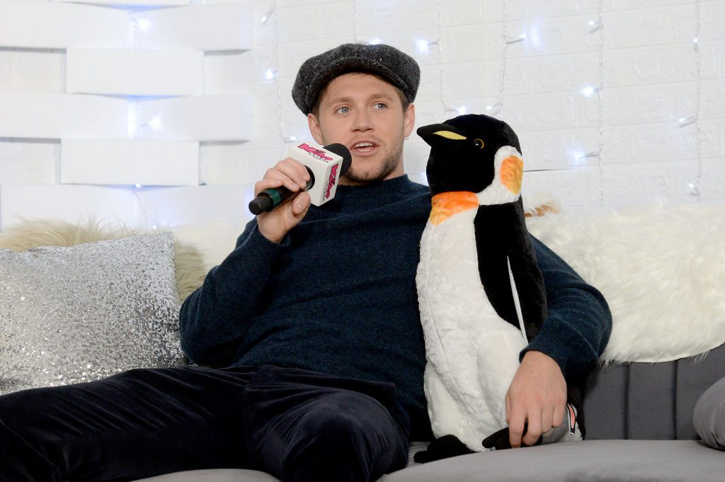 Niall Horan posing with a stuffed penguin at the iHeartRadio Jingle Ball 2019.
