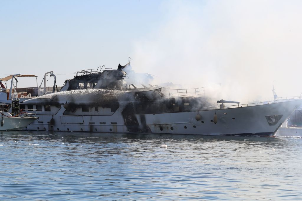 """Firefighters spray water as they try to extinguish a fire erupted during the night on board a private yacht """"Le Lalibela"""""""
