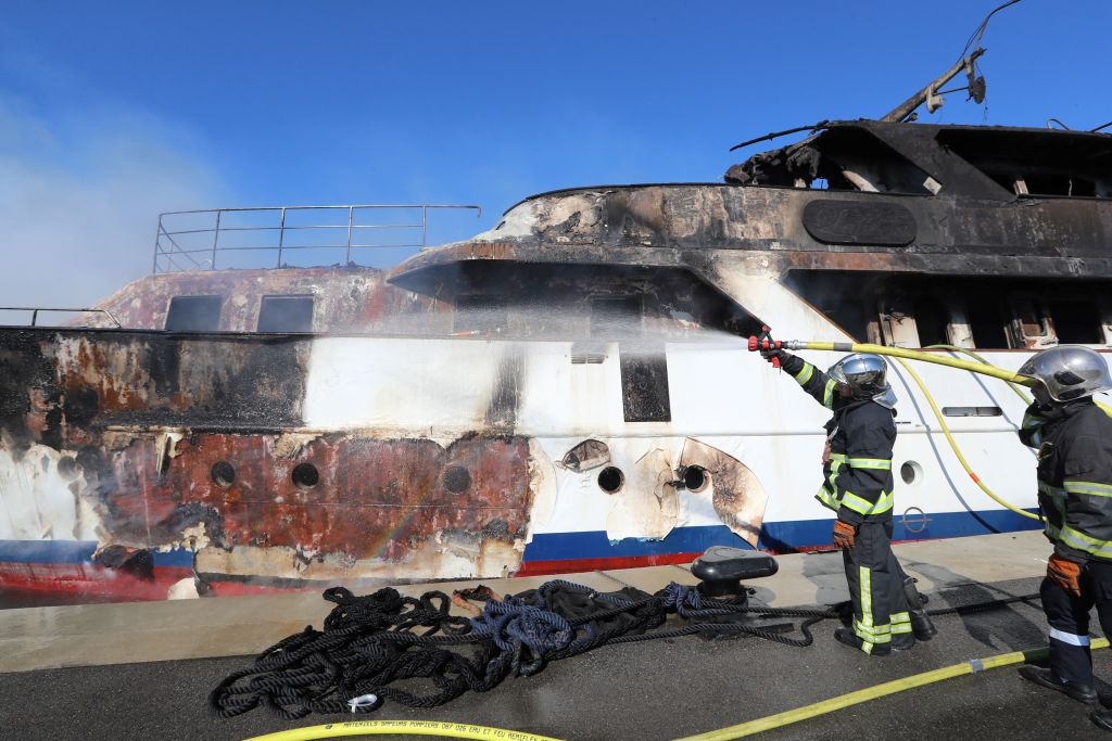 """Firefighters spray water as they try to extinguish a fire erupted during the night on board a private yacht """"Le Lalibela"""" on October 12, 2018 at the Vallauris harbour in Golf-Juan, southeastern France"""
