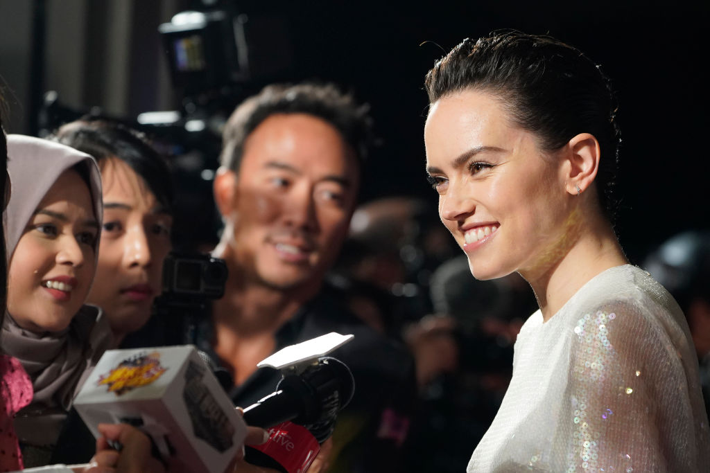 Daisy Ridley smiles for fans on the red carpet at an event for 'Star Wars: The Rise of Skywalker.'