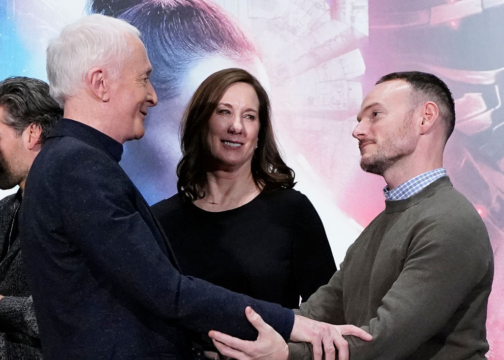 Anthony Daniels (C-3PO) and Chris Terrio share an embrace in front of Kathleen Kennedy at a press conference for 'Star Wars: The Rise of Skywalker.'