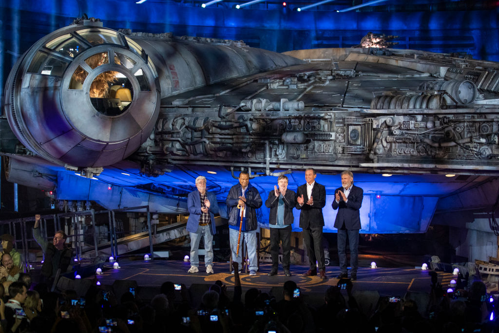 George Lucas, Billy Dee Williams, Mark Hamill, Bob Iger, and Harrison Ford in front of the Millennium Falcon at Star Wars: Galaxy's Edge in Disneyland.