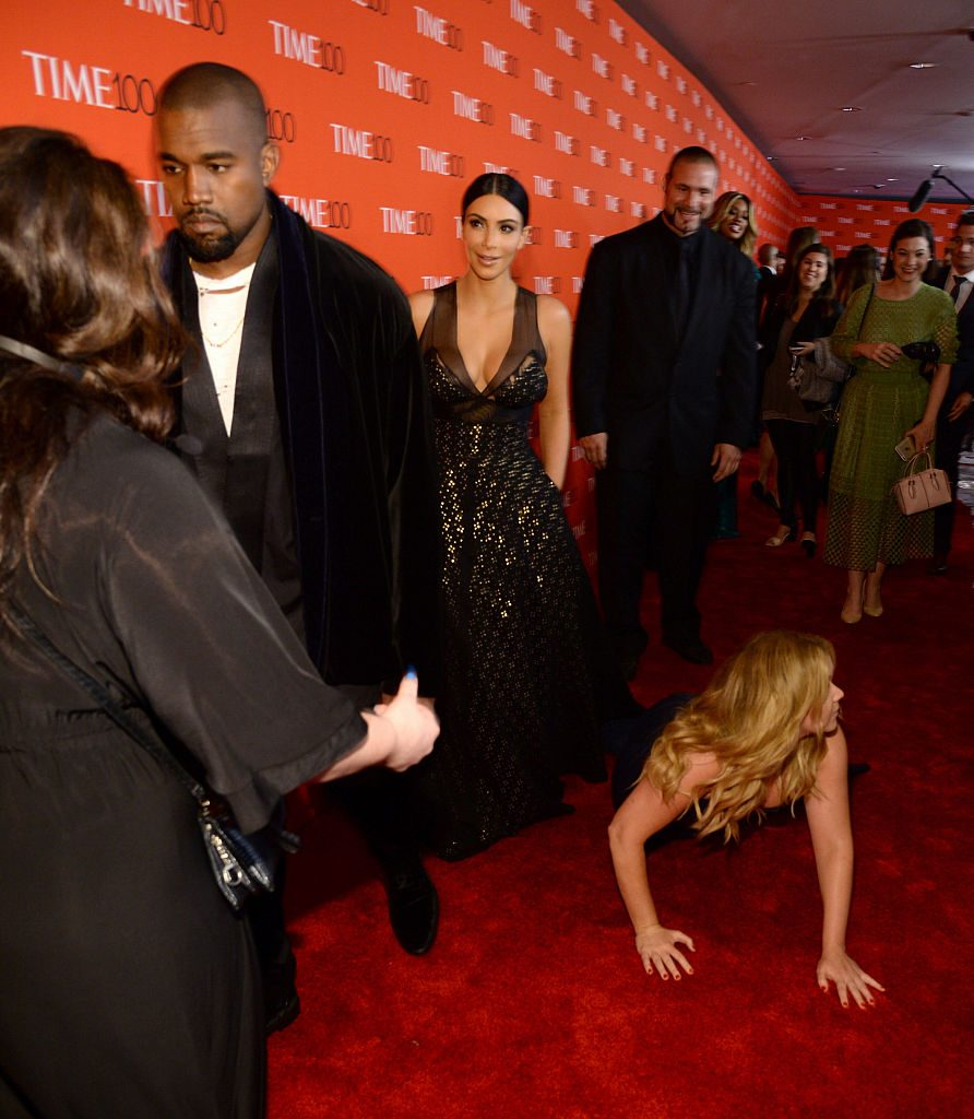 Kanye West and Kim Kardashian look on as Amy Schumer falls