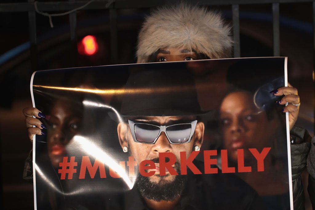 Woman holding 'Mute R Kelly' sign