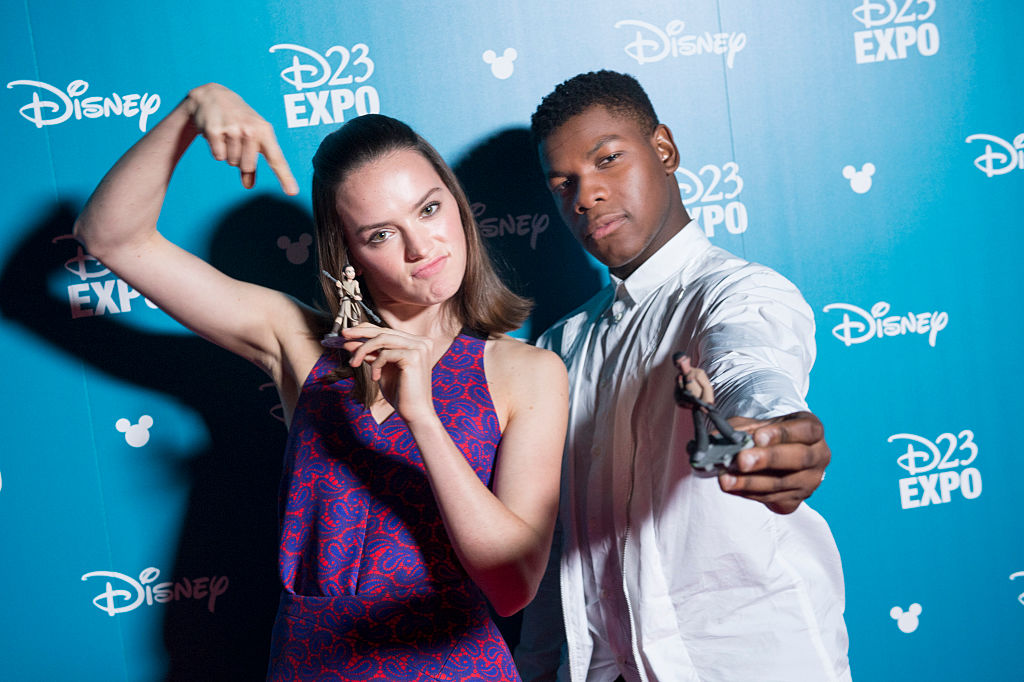 Daisy Ridley and John Boyega pose with their Disney Infinity figurines at the D23 Expo in 2015