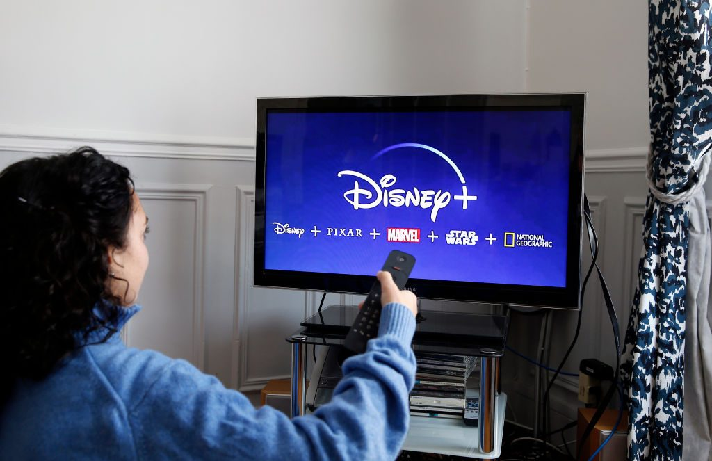 Woman with Disney+ logo on TV screen