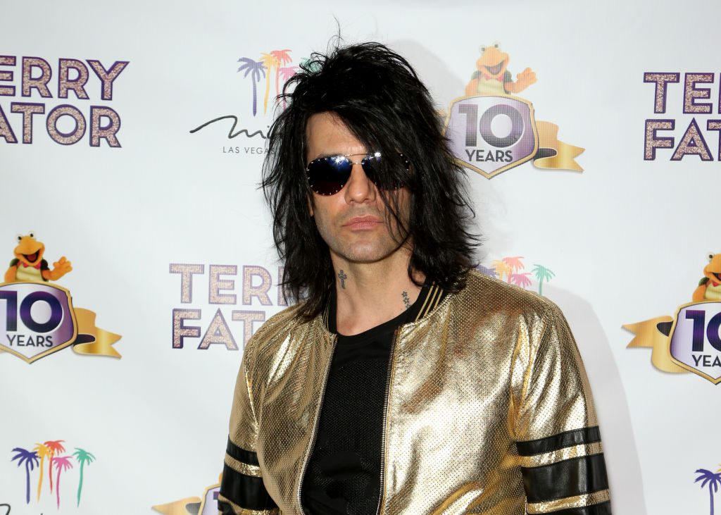 Criss Angel in sunglasses and a gold jacket in front of a repeating background