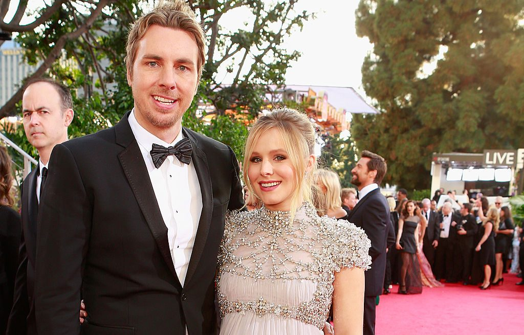 Dax Shepard and Kristen Bell smiling at a camera on the red carpet