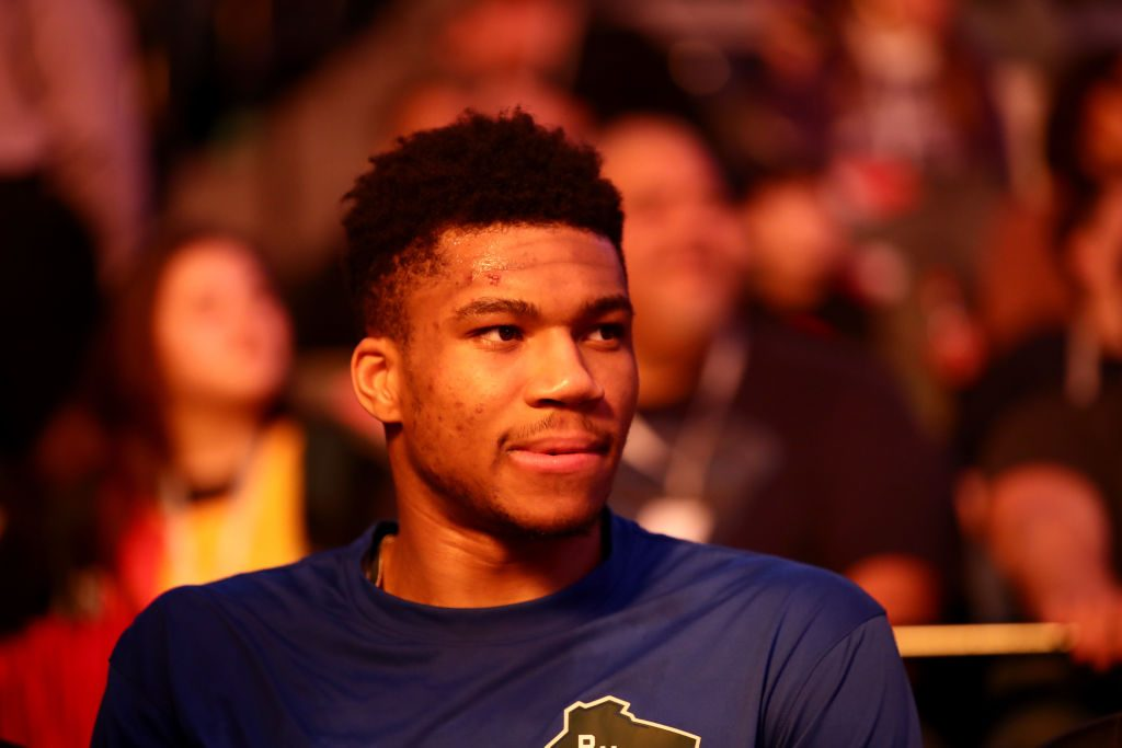 Giannis Antetokounmpo sits on the bench in a matchup between the Milwaukee Bucks and the Sacramento Kings